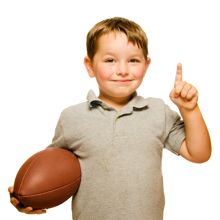 Child with football celebrating by showing that he's Number 1 is