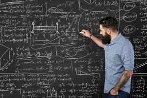 Bearded Hipster Writes Formulas On A Chalkboard